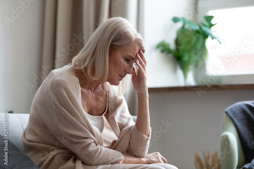 Sad mature woman sitting alone at home feeling headache depression Wallpaper Mural