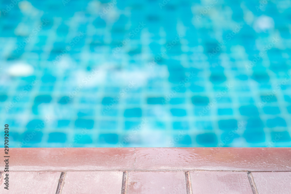 Fototapeta Outdoor swimming pool in hotel with stair or ladder and deck poolside. Summer vacation concept.