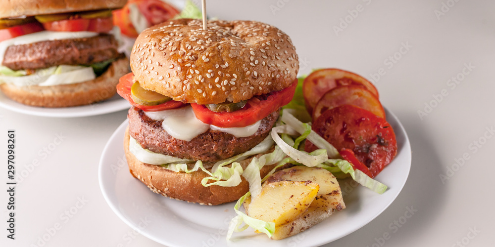 Fototapety, obrazy: Food banner: two homemade hamburgers with a juicy meat cutlet, parmesan cheese, green salad, tomatoes and fried potatoes on a light background.