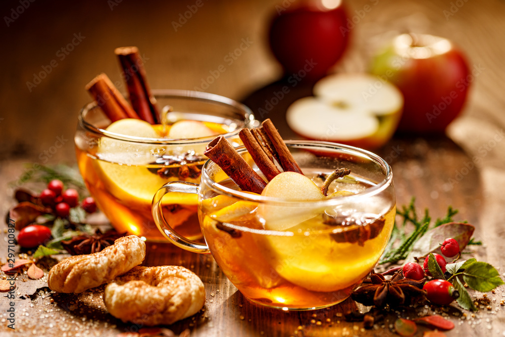Fototapeta Mulled cider with apple slices, cinnamon sticks, cloves, anise stars and citrus fruits in glass cups on a wooden rustic table. Delicious, traditional hot drink