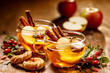 Leinwanddruck Bild - Mulled cider with apple slices, cinnamon sticks, cloves, anise stars and citrus fruits in glass cups on a wooden rustic table. Delicious, traditional hot drink
