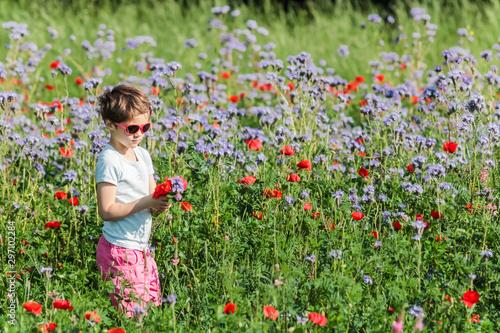 Fotografía Petite fille cueillant des fleurs dans un champ