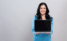 Young Woman With A Laptop Computer On A Gray Background