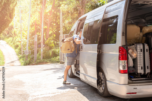 Passenger boarding on travel van with carry bag and bottle water. Fototapet