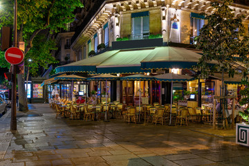 Boulevard San-German with tables of cafe in Paris at night, France