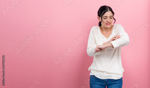 Young woman scratching her itchy arm Canvas-taulu