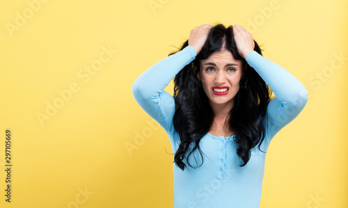 Fotografía  Young woman feeling stressed on a yellow background