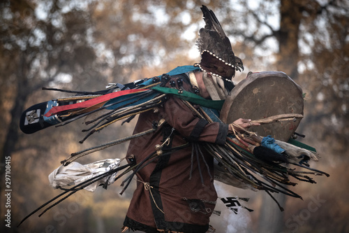 Photo Mongolian traditional shaman performing a traditional shamanistic ritual with a drum and smoke in a forest during autumn afternoon