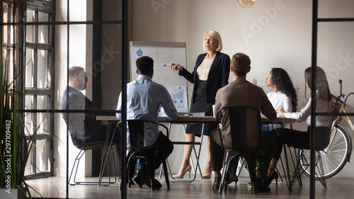 Pinturas sobre lienzo  Mature businesswoman mentor coach give flip chart presentation at workshop