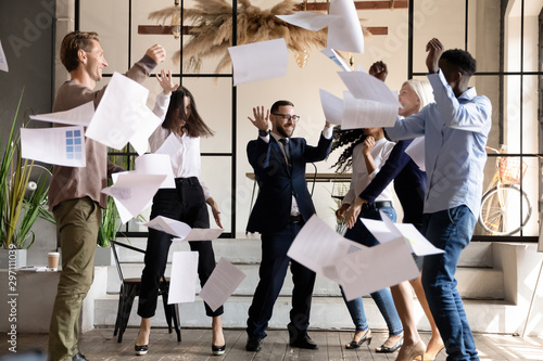 Excited happy multiracial business team dancing throwing papers in office