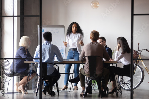 Confident african businesswoman presenter give corporate whiteboard presentation
