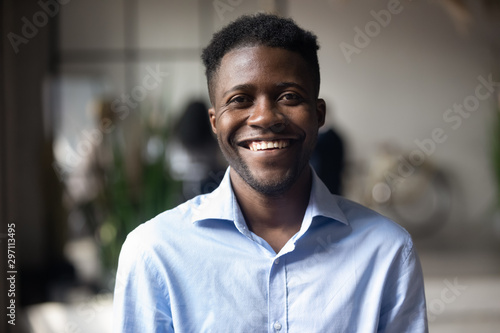 Obraz Confident smiling young african businessman looking at camera in office - fototapety do salonu