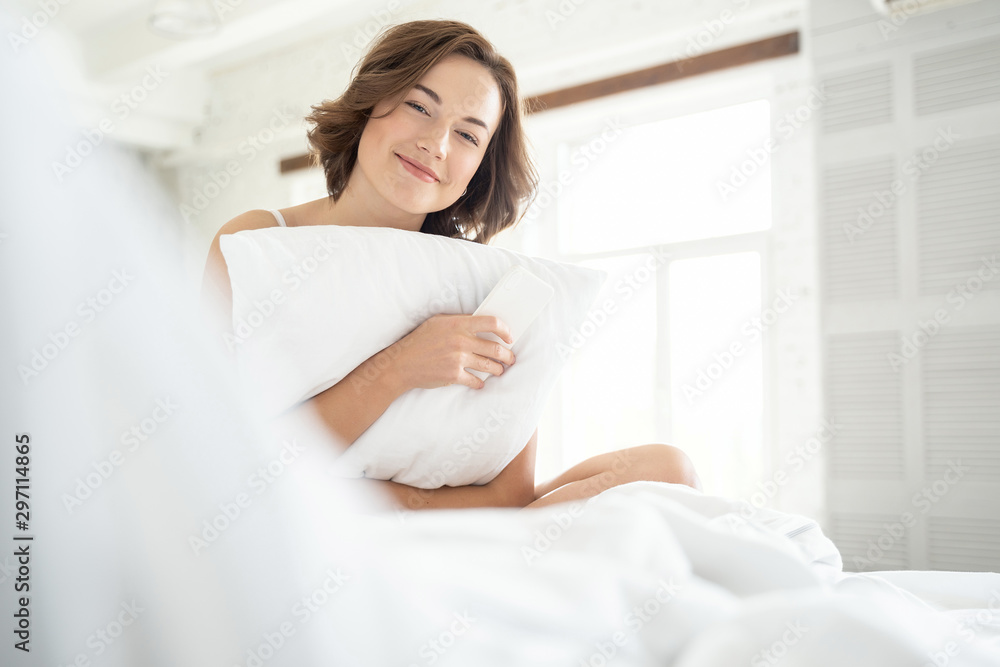 Fototapety, obrazy: Cute young happy female hugging her pillow