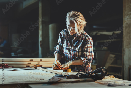 Attractive middle aged woman carpenter designer works with ruler, make notches on the tree in workshop Fototapet