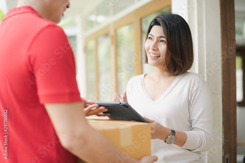 Fotografía Young Asia woman digital sign technology on tablet receiving parcel cardboard bo