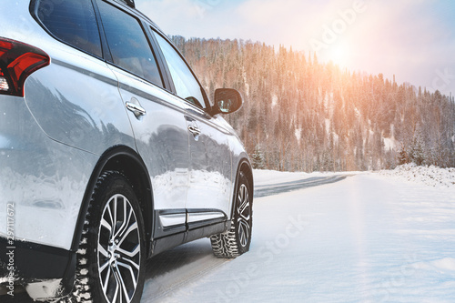Fototapeta Modern Suv four wheel drive car stay on roadside of winter road. Family trip to ski resort concept. Winter or spring holidays adventure. car on winter snowy road in mountains in sunny day. obraz