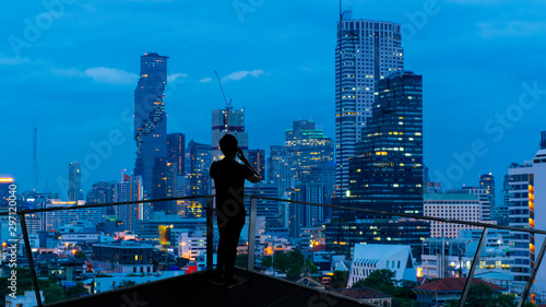 Photo Businessman standing using smart phone on open roof top balcony watching city night view