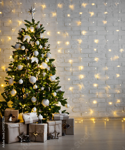 Spoed Fotobehang Kerstmis decorated christmas tree with white balls, garlands and gift boxes over white brick wall