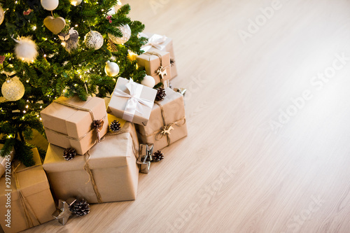Foto op Canvas Bomen christmas tree and heap of gift boxes - copy space over wooden floor background