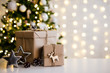 Leinwanddruck Bild christmas and new year background - gift boxes and stars near decorated christmas tree and copy space over white wall with lights