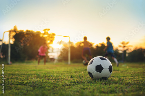 Silhouette action sport outdoors of a group of kids having fun playing soccer football for exercise at the green grass field in community rural area under the twilight sunset sky Canvas Print