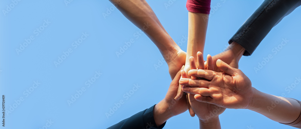 Fototapeta Teamwork of business people put their hands together in teamwork, tag team expression with copy space for text banner.