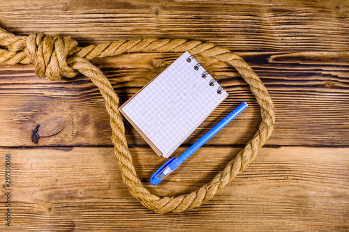 Rope with noose for the suicide, blank notepad and pen on wooden background Tablou Canvas