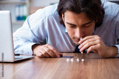 Young man having problems with narcotics at workplace Canvas Print