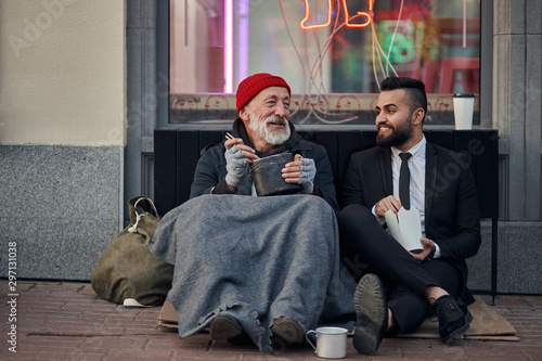 Fototapeta Handsome businessman in suit sitting on floor with homeless man together, listen to his story of life
