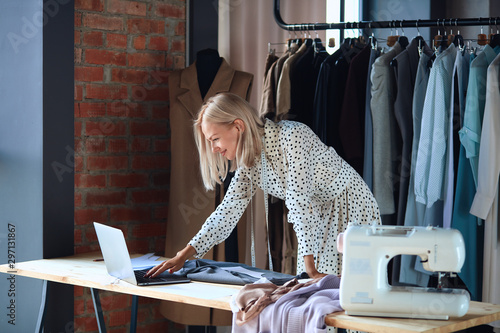 Valokuva Blonde fashion designer excitedly look at laptop while working with sketches