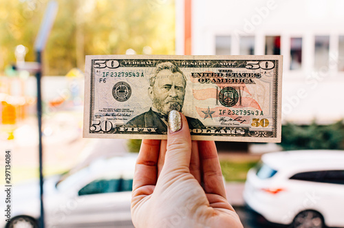 Fotografía Female hand holds 100 dollar bill against the background of the street