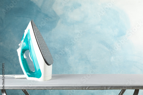 Fotografia, Obraz Iron on ironing board against blue background, space for text