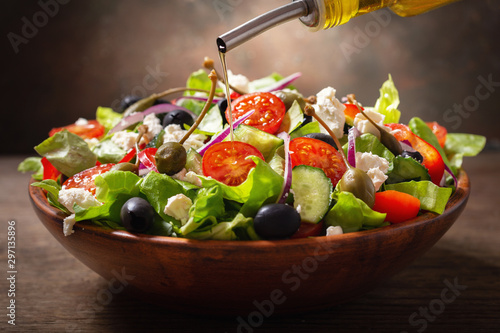olive oil pouring into bowl of fresh salad with vegetables, feta cheese and cape Fototapete
