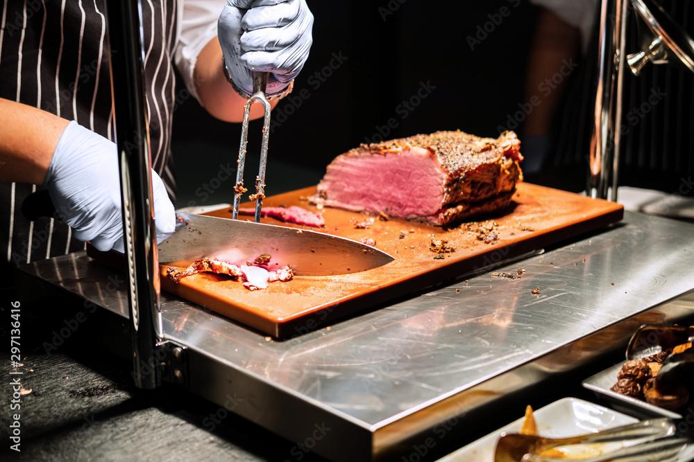 Fototapeta chef cutting meat in restaurant
