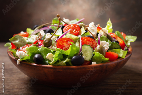 bowl of fresh salad with vegetables, feta cheese and capers