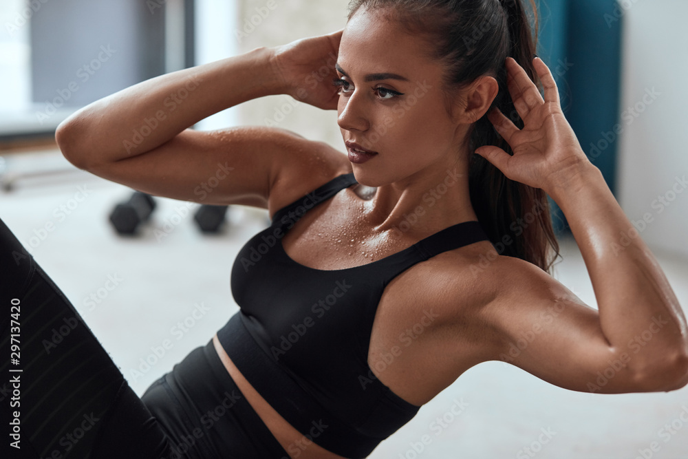 Fototapeta Slim fitness female in gym pumping press. Sweating strong fitnesswoman
