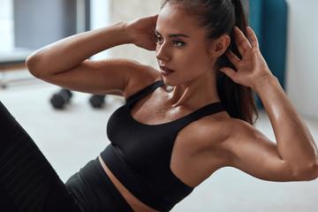 Vitka fitness žena u teretani za pumpanje preša. Znoji se snažna fitness žena