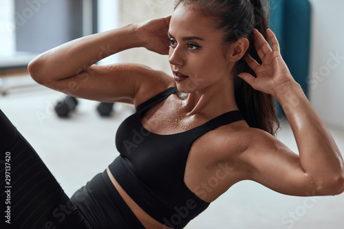Fototapeta Slim fitness female in gym pumping press. Sweating strong fitnesswoman obraz