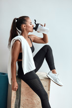 Profile Of Beautiful Slim Female Drinking Water And Having Rest After Fitness, Pilates. White Towel In Shoulders