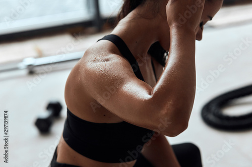 Fit woman with strong muscles after active training in fitness gym Fototapet