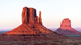 Panoramic view of two mittens butte mesa with colorful red orange rock color on horizon in Monument Valley canyons during sunset in Arizona