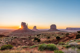 Wide angle overlook panoramic view of buttes and horizon in Monument Valley at sunrise colorful light and sunburst in Arizona with orange rocks