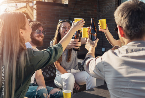 Fototapety, obrazy: Jolly friends drinking beer during Friday evening party on a loft balcony