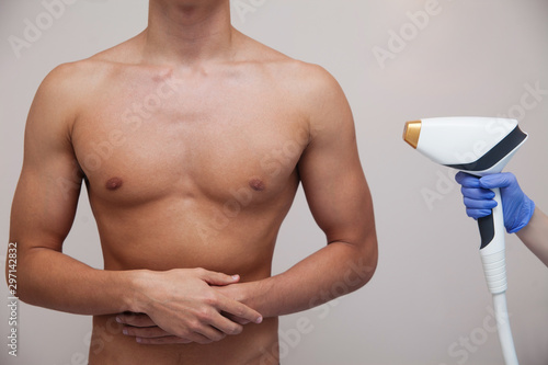 Obraz Muscular athlete man with smooth clear skin. Epilation and depilation of hair in beauty salon. Male laser hair removal concept. Beautician using modern apparatus for procedures. Skin and Beauty Care - fototapety do salonu