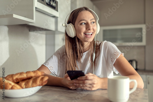 Pretty cheerful young woman enjoying her morning coffee with croissants and her Fototapete