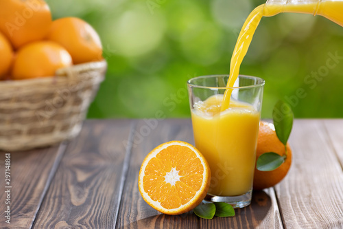 Fototapeta orange juice pouring in glass obraz