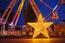Illuminated Glowing Star In Amusement Park At The Night City