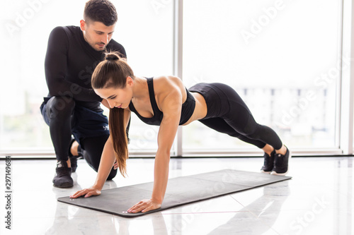 Tablou Canvas Sporty young couple doing plank exercise in gym