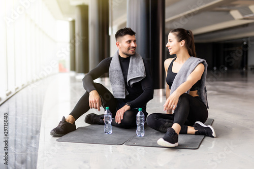 Young healthy couple relaxing after workout in the gym Fototapet