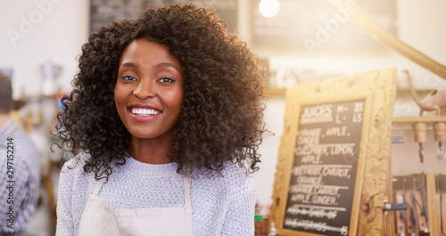 Fotografía  Smiling African American entrepreneur barista standing in a bright cafe